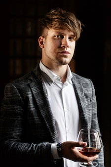 Handsome young man in grey suit stands with a glass of whisky