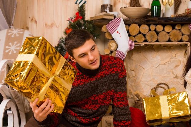 彼がそれを振るときに彼の耳に金で包まれた箱を持って彼のクリスマスプレゼントを推測しているハンサムな若い男
