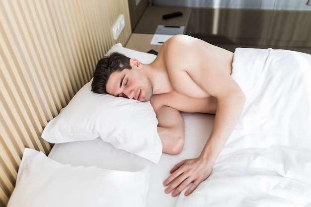 Handsome young man happily sleeping in white bed, isolated.