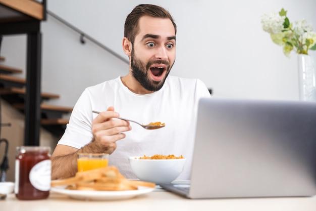 Красивый молодой человек завтракает, сидя на кухне, используя портативный компьютер