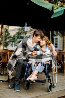 Handsome young man having some coffee and dating with woman on a wheelchair on a sunny day