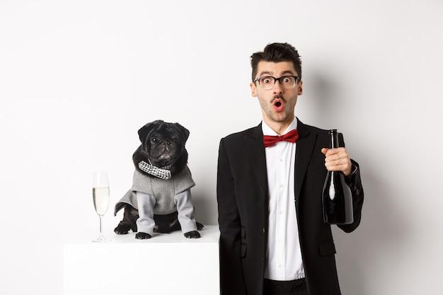 Bel giovane e il suo cucciolo che celebrano le vacanze di capodanno, carlino nero e proprietario del cane in piedi in giacca e cravatta, ragazzo che tiene champagne, sfondo bianco.