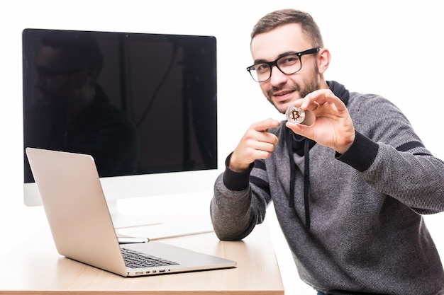 Handsome young man at his working place with laptop and pc monitor screen on back pointed on bitcoin