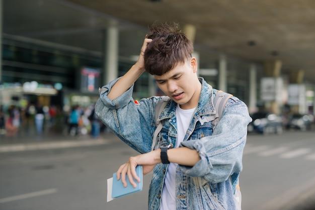 잘생긴 청년은 손에 머리를 잡고 시계를 보고 있다