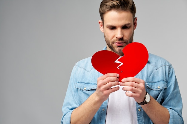 Handsome young man holding broken paper red valentine heart standing over grey