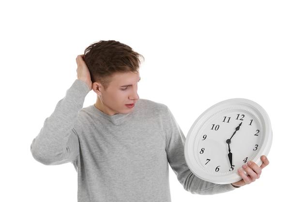 Красивый молодой человек, держащий часы, на белом