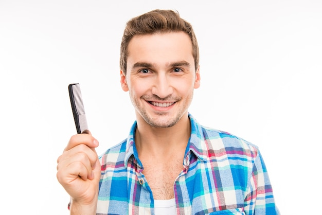 Handsome young man holding a comb isolated