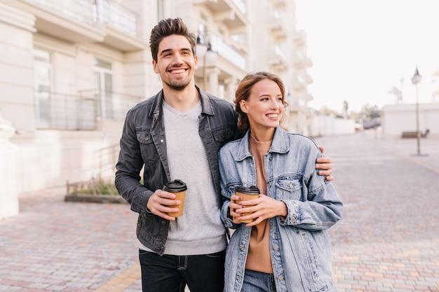 커피 한잔 들고와 포용 여자 친구 잘 생긴 젊은 남자. 야외 데이트를 즐기는 웃는 커플.