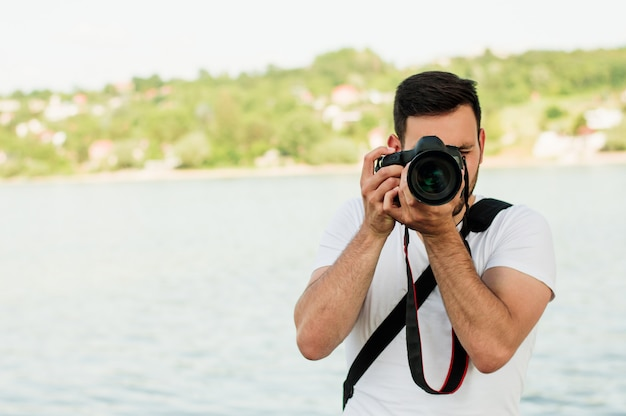 Handsome young man holding a dslr camera.