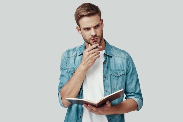 Красивый молодой человек держит блокнот и держит руку на подбородке, стоя на сером фоне