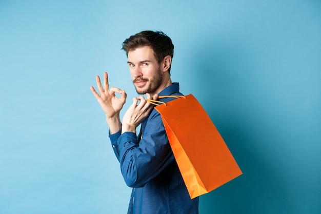 肩に買い物袋を持っているハンサムな若い男は、カメラを見て、大丈夫なジェスチャーを示すために振り返って、お店、青い背景をお勧めします。