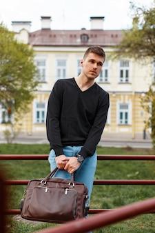 Красивый молодой человек в черной футболке с кожаной сумкой, на открытом воздухе