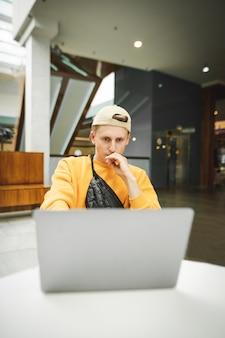 キャップと黄色のユリでハンサムな若い男はコンピューターで動作します