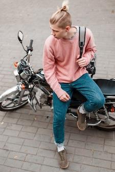 Красивый молодой человек в розовом модном свитере и синих джинсах с рюкзаком сидит на мотоцикле