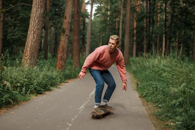 Красивый молодой человек в розовом свитере и синих джинсах катается на скейтборде по асфальту в парке