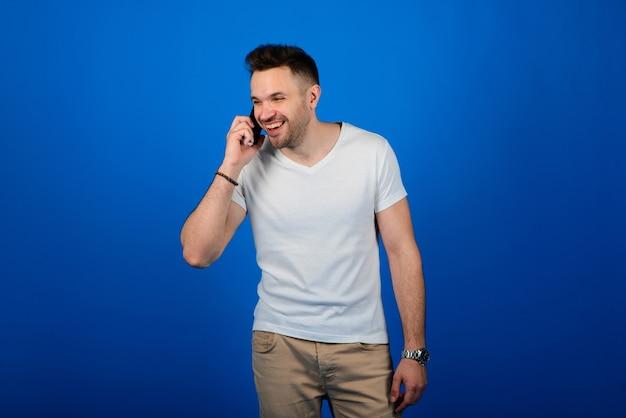 スマートフォンを持って笑顔でカメラを見てスマートカジュアルな服装のハンサムな若い男