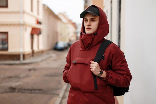 검은 배낭 유행 모자에 후드와 함께 세련된 빨간색 긴 재킷에 잘 생긴 젊은 남자가 빈티지 하우스 근처 도시를 산책