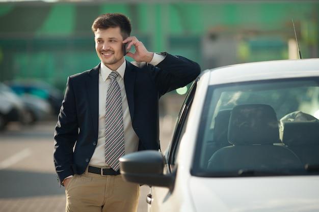Красивый молодой человек в костюме разговаривает по телефону на улице возле машины