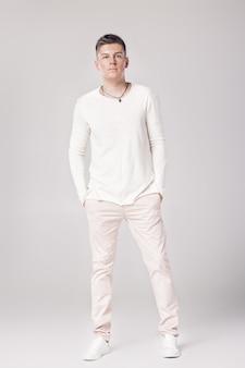白いセーターを着たハンサムな若い男がポーズをとっている