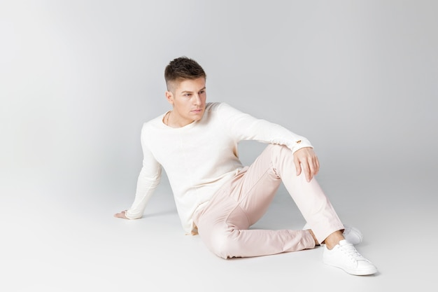 흰색 스웨터 포즈에 잘 생긴 젊은 남자