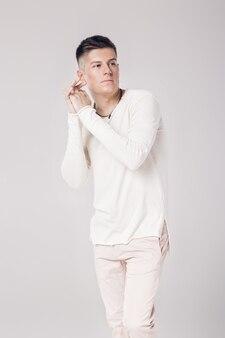 白いセーターを着たハンサムな若い男がちょっと考えた