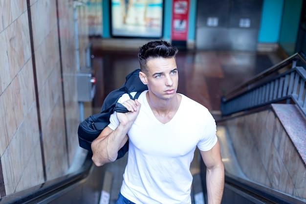 肩にバッグを運ぶ白いtシャツでハンサムな若い男