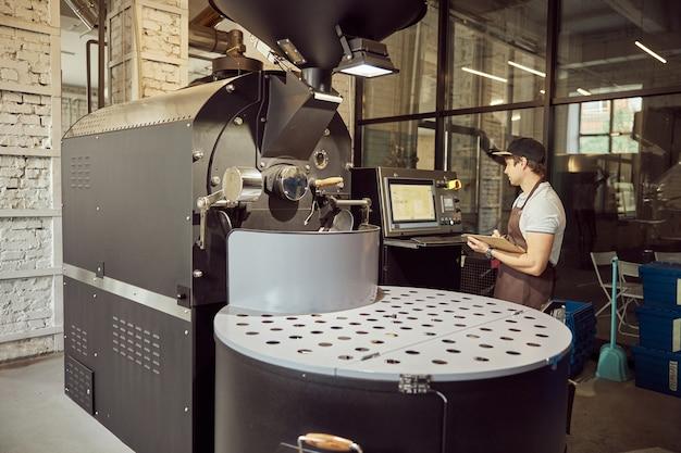 클립 보드를 들고 전문 커피 로스팅 장비에 서있는 동안 제어판을보고 앞치마에 잘 생긴 젊은 남자