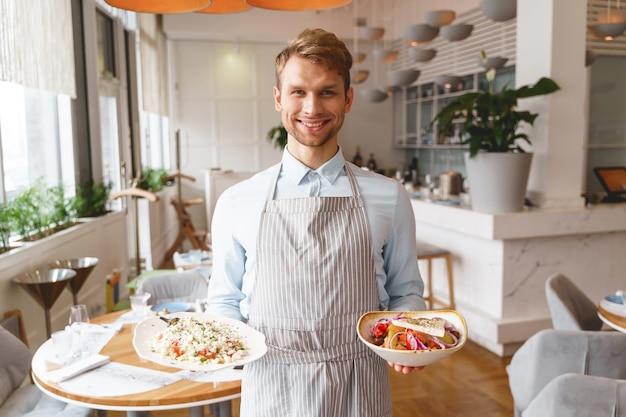 Красивый молодой человек в фартуке смотрит и улыбается, держа в руках вкусные свежие салаты