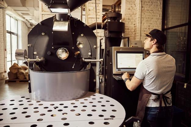 제어판에 서있는 동안 전문 커피 로스팅 장비를보고 앞치마에 잘 생긴 젊은 남자