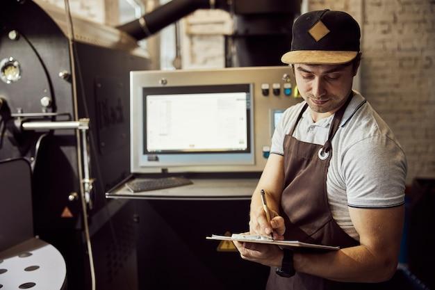 커피 로스팅 기계의 제어판 근처에 서있는 동안 메모를하는 앞치마에 잘 생긴 젊은 남자