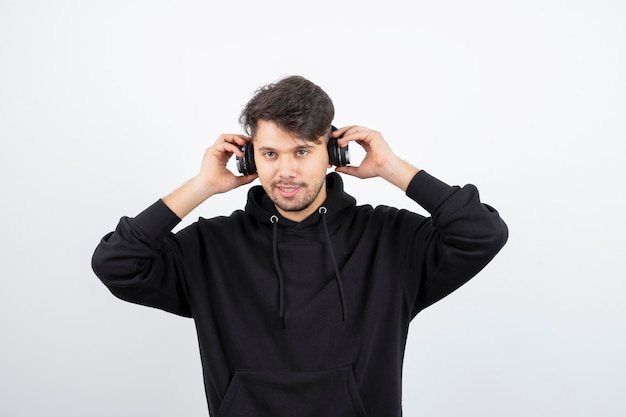 大きなワイヤレス音楽ヘッドフォンを身に着けている黒いパーカーのハンサムな若い男
