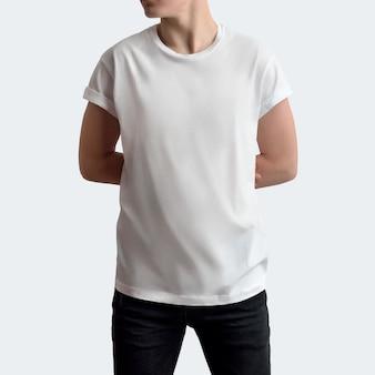 흰색 빈 스튜디오 배경에 빈 티셔츠와 검은색 바지를 입은 잘생긴 청년. 팔을 뒤로 하고 정면 포즈. 모형은 쇼케이스에서 사용할 수 있습니다.