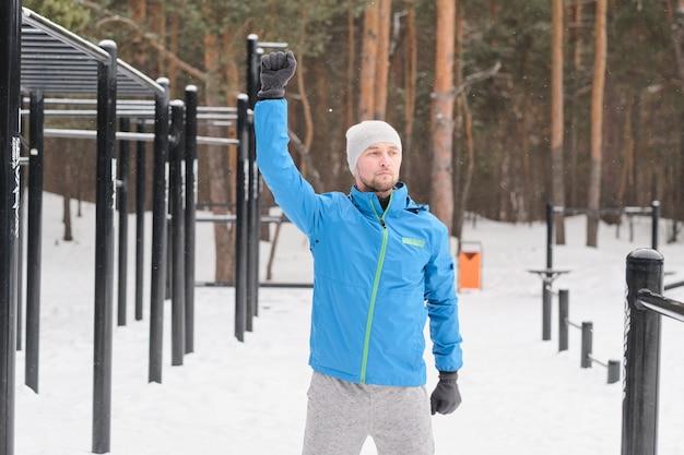 冬の運動場でトレーニング中に肩の可動性運動をしている青いジャケットのハンサムな若い男