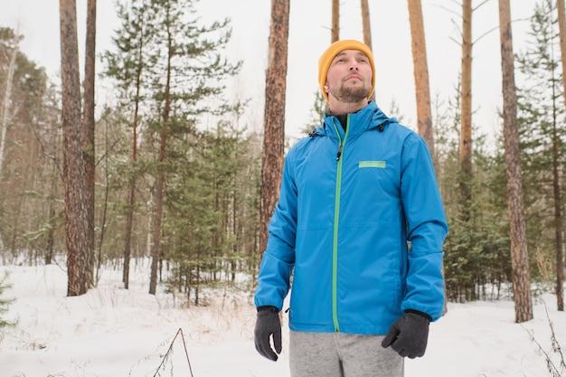 青いジャケットを着たハンサムな若い男が周りを見回し、森の冬の散歩を楽しんでいます