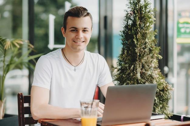 캐주얼 복장에 잘 생긴 젊은 남자가 웃고 멋진 야외 카페에 앉아 노트북을 탐색하는 동안 카메라를보고