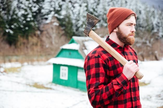 Красивый молодой человек в клетчатой рубашке и шляпе с топором гуляет по деревне