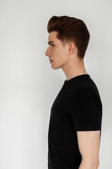 세련된 헤어스타일을 한 세련된 검은색 티셔츠를 입은 잘생긴 청년은 스튜디오의 흰 벽 근처에 서 있습니다. 실내에서 세련된 캐주얼 옷을 입은 매력적인 남자 패션 모델. 신선한 프로필 사진입니다.