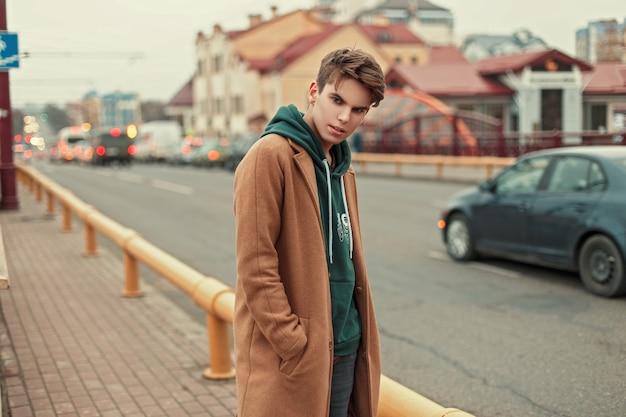 코트와 까마귀 도로 근처 거리에서 포즈에 잘 생긴 젊은 남자