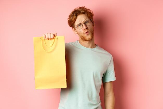 カメラを生意気に見て、黄色の買い物袋を見せて、店の割引について話し、ピンクの背景の上に立っている眼鏡をかけたハンサムな若い男