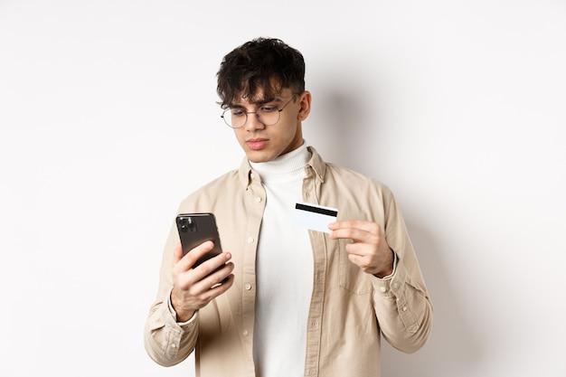 電話で購入、オンラインショッピング、プラスチックのクレジットカードとスマートフォンを持って、白い壁に立っている眼鏡をかけたハンサムな若い男。