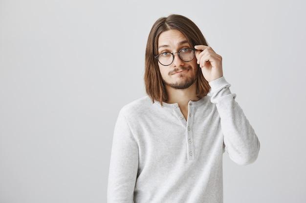 Красивый молодой человек в очках ухмыляется