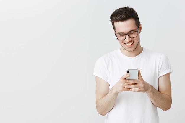 Красивый молодой человек в очках с помощью мобильного телефона