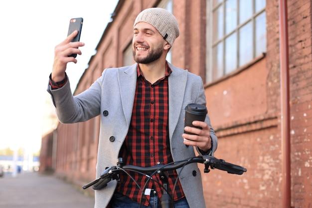 회색 코트와 모자를 쓰고 커피를 마시고 셀카를 찍는 거리에 서서 걷고 있는 잘생긴 청년.
