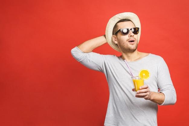 Красивый молодой человек в шляпе и солнечных очках пьет свежий апельсиновый сок на красном фоне