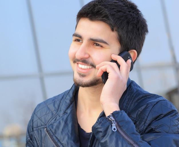 電話で話している私服のハンサムな若い男。