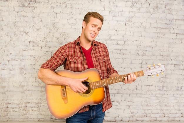 ギターを弾いて歌う赤いシャツを着たハンサムな若い男