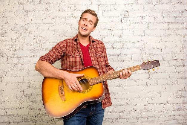 기타를 연주하고 노래하는 빨간 셔츠에 잘 생긴 젊은 남자