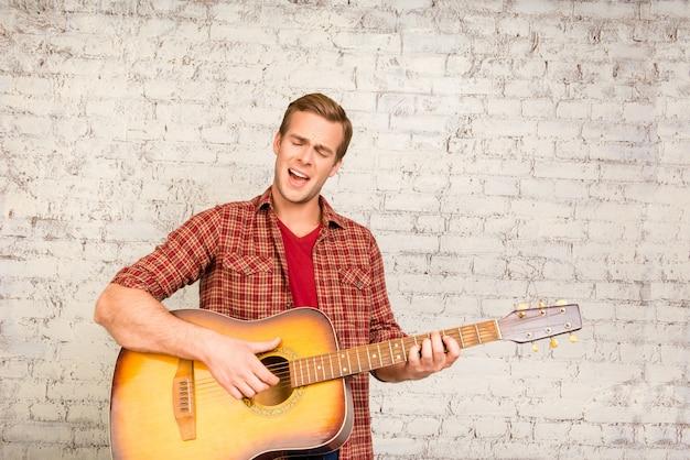 ギターで遊ぶ赤いシャツのハンサムな若い男