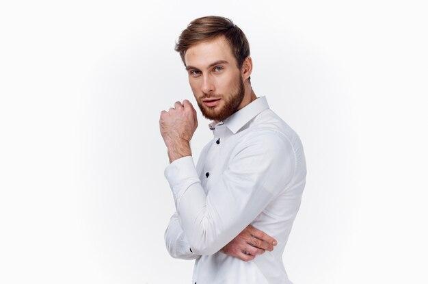 シャツを着たハンサムな若い男は、手の側面図の明るい背景で彼の顔に触れます