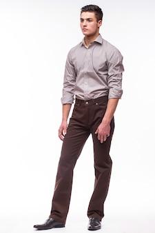 Красивый молодой человек в рубашке, стоя у белой стены
